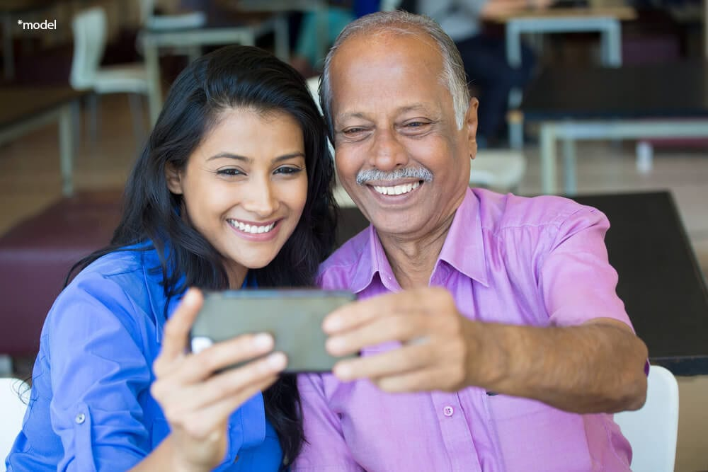 Older man and young woman smiling while looking at a cell phone.
