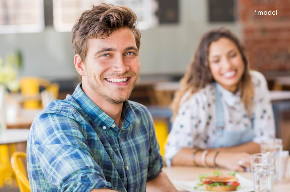 Young man and woman smiling at camera.