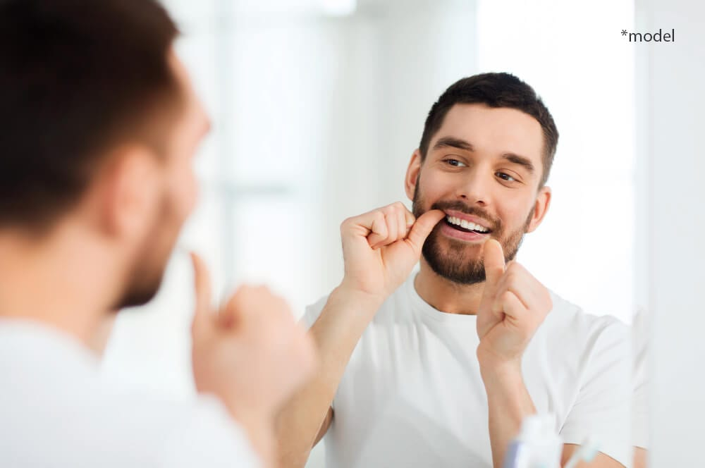 Man looking in mirror and flossing teeth.
