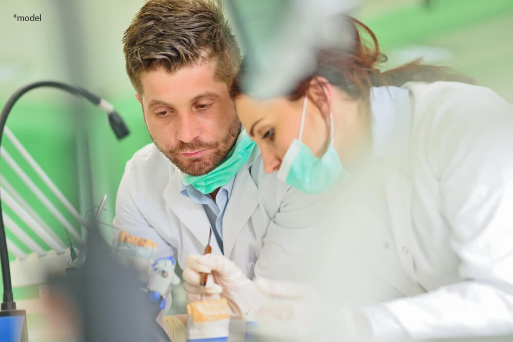 Dentists working on prosthetic teeth.
