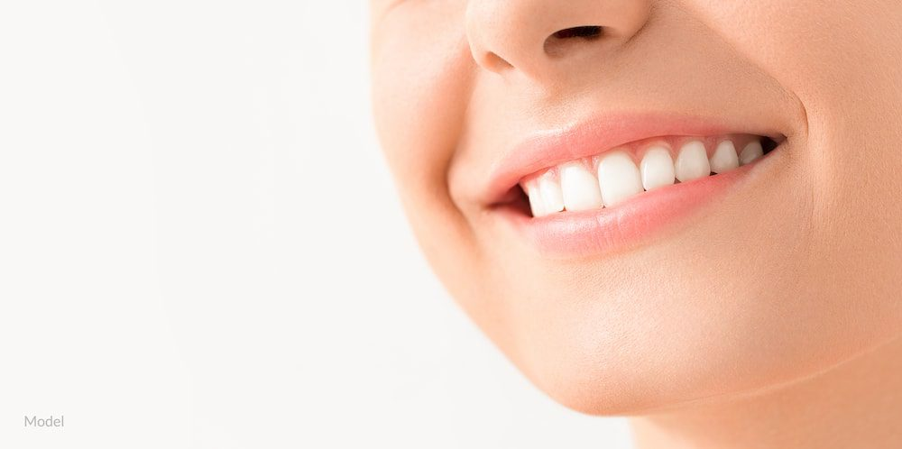 Woman smiling with healthy, white teeth and no signs of periodontal disease.