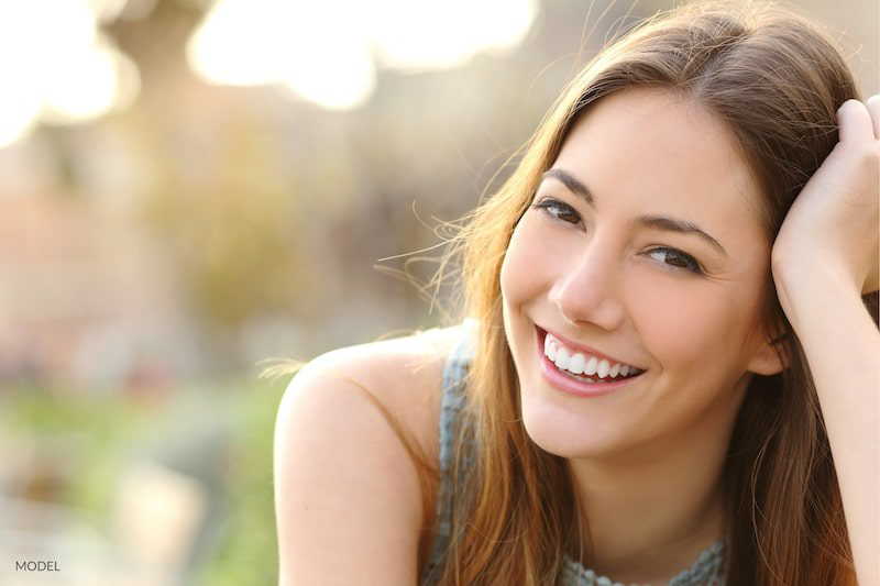 Woman with white teeth smiling outdoors