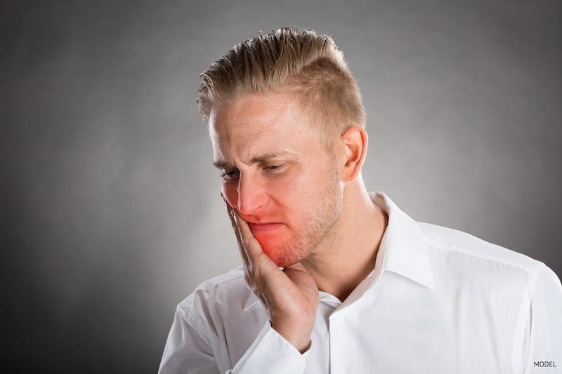 man dealing with jaw pain due to a tooth emergency.