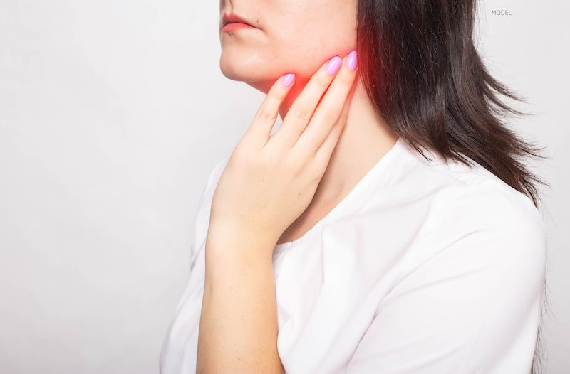 Woman with hand on a neck, which is glowing red to demonstrate jaw and neck pain.