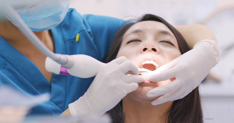 Woman getting a dental cleaning at dentist office